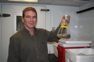 Dan Shain holds a container of glacial ice worms.