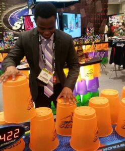 Muthangya tests a cup stacking game at the annual Toy Fair.