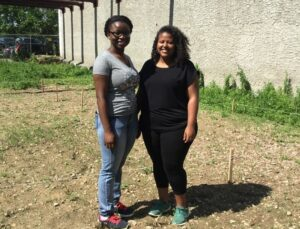 Rutgers-Camden senior biology major Aisha Dorley (left) and master's student Timnit Kefela stand on a vacant lot in Camden where they are working to invigorate the soil and create an ecosystem complete with wildflowers that attract pollinator insects.