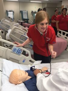 Sophomore nursing student Tabitha Summers listens to a simulation manikin's heartbeat.
