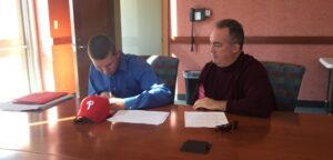 Jeff Singer (left) signs with the Phillies as agent Jim Ulrich looks on.