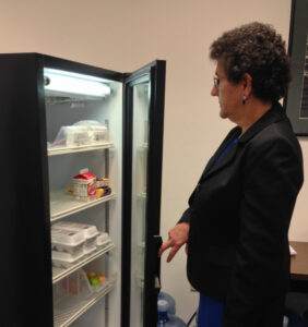 Maria Serra, Director of Student Health Services checking the Raptor Pantry refrigerator