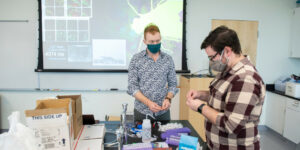 """Nathan Fried and Ed Waddell assemble items for the """"lab in a box"""""""