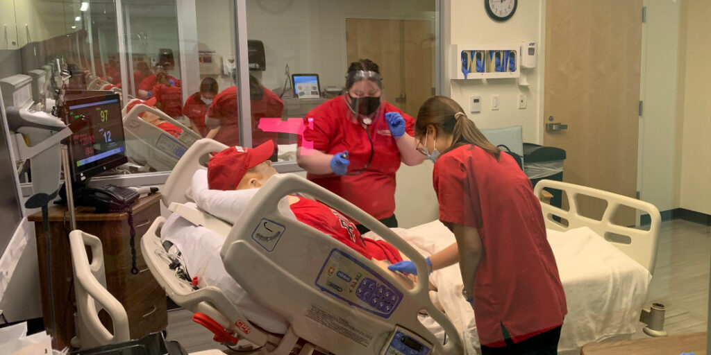 Students Hanna Monteleone and Weiji Zhang training to work with patients in the simulation lab