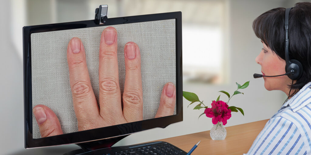 Medical professional looking at a patient's hand during telemedicine appointment
